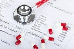 Cápsulas vermelhas do estetoscópio e do comprimido que colocam no formulário médico Fotos de Stock