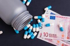 Cápsulas y dinero en circulación europeo Imágenes de archivo libres de regalías