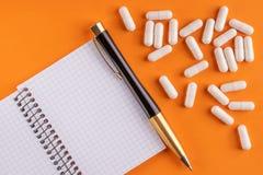 Cápsulas y píldoras médicas alrededor del cuaderno en blanco con la pluma en el fondo anaranjado, cierre para arriba foto de archivo
