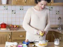 Cáscara de limón de rejilla de la mujer joven para hacer las magdalenas Fotografía de archivo libre de regalías