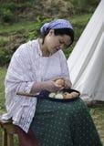 Cáscara de onions de la mujer que se sienta en banco de madera Fotos de archivo libres de regalías