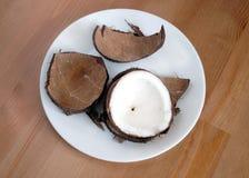 Cáscara del coco y fruta machacadas del coconau en el primer blanco de la placa Imágenes de archivo libres de regalías