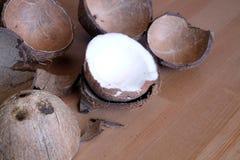 Cáscara del coco y fruta machacadas del coconau en fondo de madera Imagen de archivo