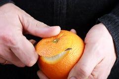 Cáscara del hombre una naranja Foto de archivo