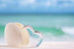 Cáscara del mar blanco con el vidrio del corazón en backgrou del azul de la playa y del mar imagen de archivo libre de regalías