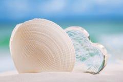 Cáscara del mar blanco con el vidrio del corazón en backgrou del azul de la playa y del mar imágenes de archivo libres de regalías