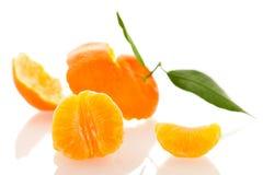 Cáscara espiral del mandarín anaranjado con las hojas verdes y una rebanada de c Foto de archivo libre de regalías