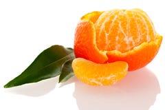 Cáscara espiral del mandarín anaranjado con las hojas verdes y una rebanada de c Fotos de archivo