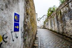 Cáscara y flecha amarillas de concha de peregrino en una pared que firma la manera a Santiago de Compostela en Galicia foto de archivo