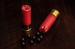 Cáscaras de escopeta rojas en una superficie de madera Fotos de archivo libres de regalías
