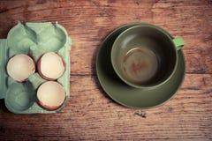 Cáscaras de huevo y taza vacía fotografía de archivo