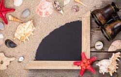 Cáscaras del mar con las estrellas de mar binoculares y chakboard Foto de archivo