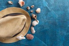 Cáscaras del mar, sombrero de la playa en fondo de madera azul Fotografía de archivo libre de regalías
