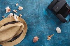 Cáscaras del mar, sombrero de la playa y cámara de la foto en fondo de madera azul Imagen de archivo libre de regalías