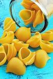 Cáscaras grandes de las pastas en un tarro de cristal en fondo azul Imagen de archivo libre de regalías