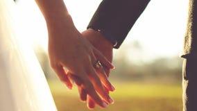 Cáseme hoy y diario Pares del recién casado que llevan a cabo las manos, tiro en la cámara lenta metrajes