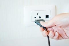 Câble électrique avec la main et le débouché électrique Photo stock