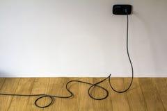 Câble électrique noir dans la prise murale sur le plancher de parquet en bois Photo stock