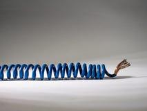 Câble bleu tordu sur le fond blanc fil isolé électrique images libres de droits