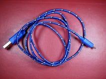 Câble d'USB dans la tresse bleue avec les points blancs sur le fond rouge photographie stock