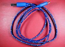 Câble d'USB dans la tresse bleue avec les points blancs sur le fond rouge photos stock