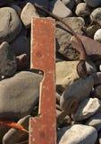 C?ble en bois de planche et en m?tal sur la plage rocheuse photographie stock libre de droits