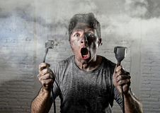 Câble non formé d'homme étant victime de l'accident électrique avec le visage brûlé sale dans l'expression drôle de choc Photographie stock libre de droits