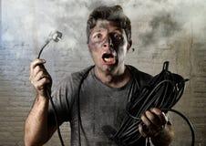 Câble non formé d'homme étant victime de l'accident électrique avec le visage brûlé sale dans l'expression drôle de choc Photographie stock
