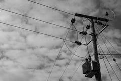 Câbles à haute tension et transformateur de courant électrique vu érigés sur un poteau en bois Images stock