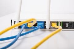 Câbles Ethernet jaunes et bleus dans le routeur sans fil Image libre de droits