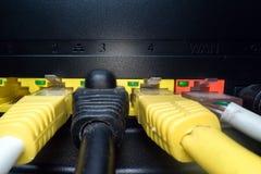 Câbles multicolores de réseau insérés dans le panneau de routeur sur un fond foncé Connexion internet, industrie de communic photographie stock