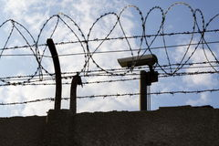Câmara de segurança atrás da cerca do arame farpado em torno das paredes da prisão Fotografia de Stock Royalty Free