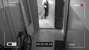 A câmara de vigilância travou o ladrão em uma máscara que foge com um saco da pilhagem filme