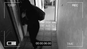 A câmara de vigilância travou o ladrão em uma máscara que foge com um saco da pilhagem imagem de stock