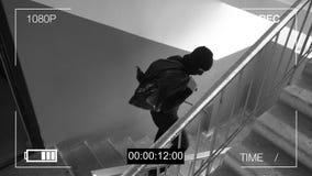 A câmara de vigilância travou o ladrão em uma máscara que foge com um saco da pilhagem imagens de stock