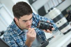 Câmara digital da lente da limpeza do homem com escova especial Fotos de Stock