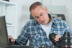 Câmara digital da lente da limpeza do homem com escova especial Fotos de Stock Royalty Free