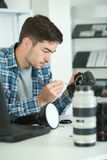 Câmara digital da lente da limpeza do homem com escova especial Fotografia de Stock