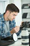 Câmara digital da lente da limpeza do homem com escova especial Imagens de Stock Royalty Free