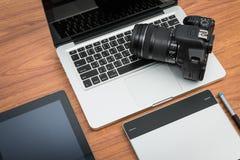 Câmara digital de DSLR com o portátil da tabuleta e do caderno Imagens de Stock Royalty Free