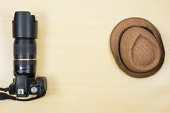 Câmara digital e chapéu na tabela de madeira para o curso Fotos de Stock Royalty Free