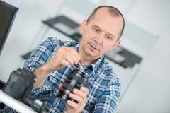 Câmara digital madura da lente da limpeza do homem com escova especial Fotos de Stock Royalty Free
