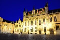 A câmara municipal e o Burg de Bruges esquadram na noite, Bélgica Foto de Stock