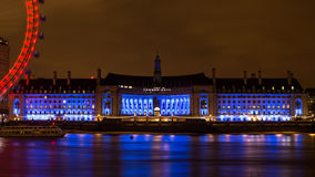 A câmara municipal iluminada de Southbank reflete em um Thames River macio Foto de Stock Royalty Free