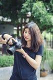 Câmera asiática bonita da terra arrendada da mulher no jardim imagem de stock