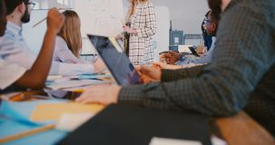 A câmera aumenta acima da tabela de reunião da equipe, mulher de negócio loura positiva bem sucedida que fala à equipe dos colega vídeos de arquivo