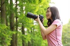 A câmera chinesa da posse do fotógrafo da mulher de Aisan perto de seu trabalho da cara na natureza disparou em plantas verdes do imagens de stock