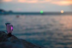 A câmera da ação com o diodo cor-de-rosa luminoso está na rocha sobre o mar da noite O indicador da bateria do dispositivo ilumin Foto de Stock