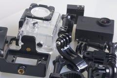 A câmera da ação encontra-se em uma superfície branca A câmera da ação encontra-se em uma superfície branca Perto da caixa para o Fotos de Stock