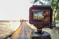 A câmera da ação montou em um tripé e faz um lapso de tempo do cais e do nascer do sol fotografia de stock royalty free